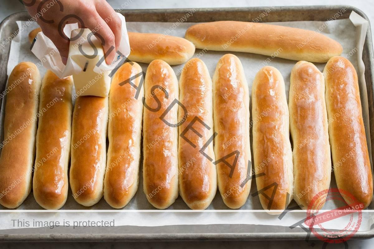 Unte con mantequilla los palitos de pan en una bandeja para hornear con un trozo de mantequilla.