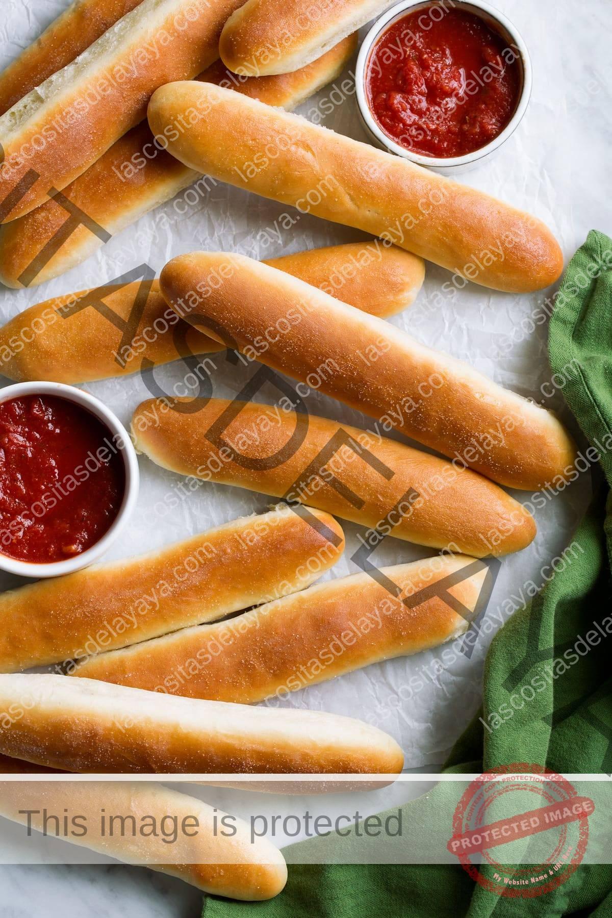 Palitos de pan esparcidos sobre el pergamino con los lados de la salsa marinara.