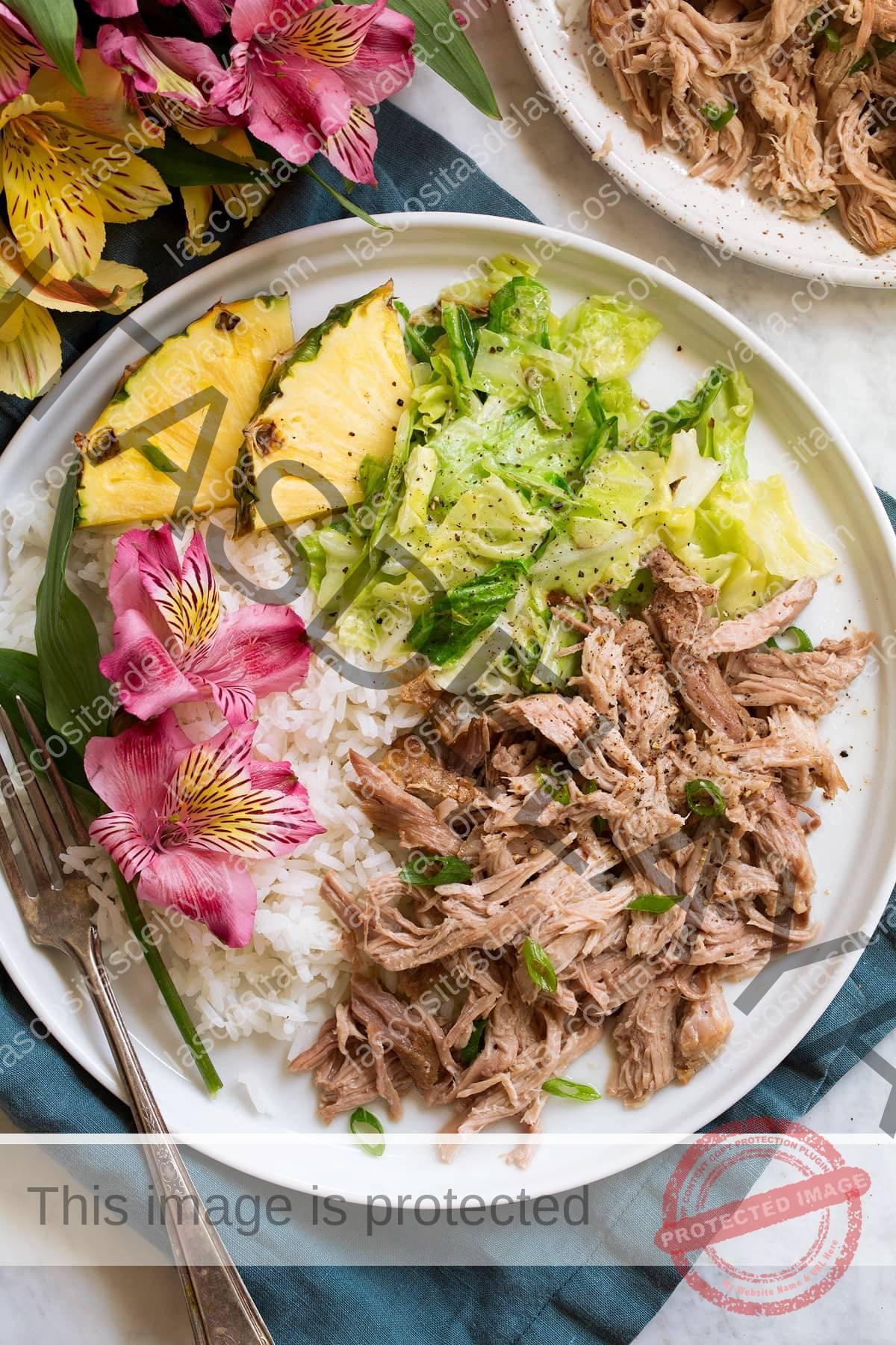 Porción única de cerdo kalua desmenuzado en un plato de servir blanco, ilustrado con arroz blanco, repollo estofado, piña fresca y flores.