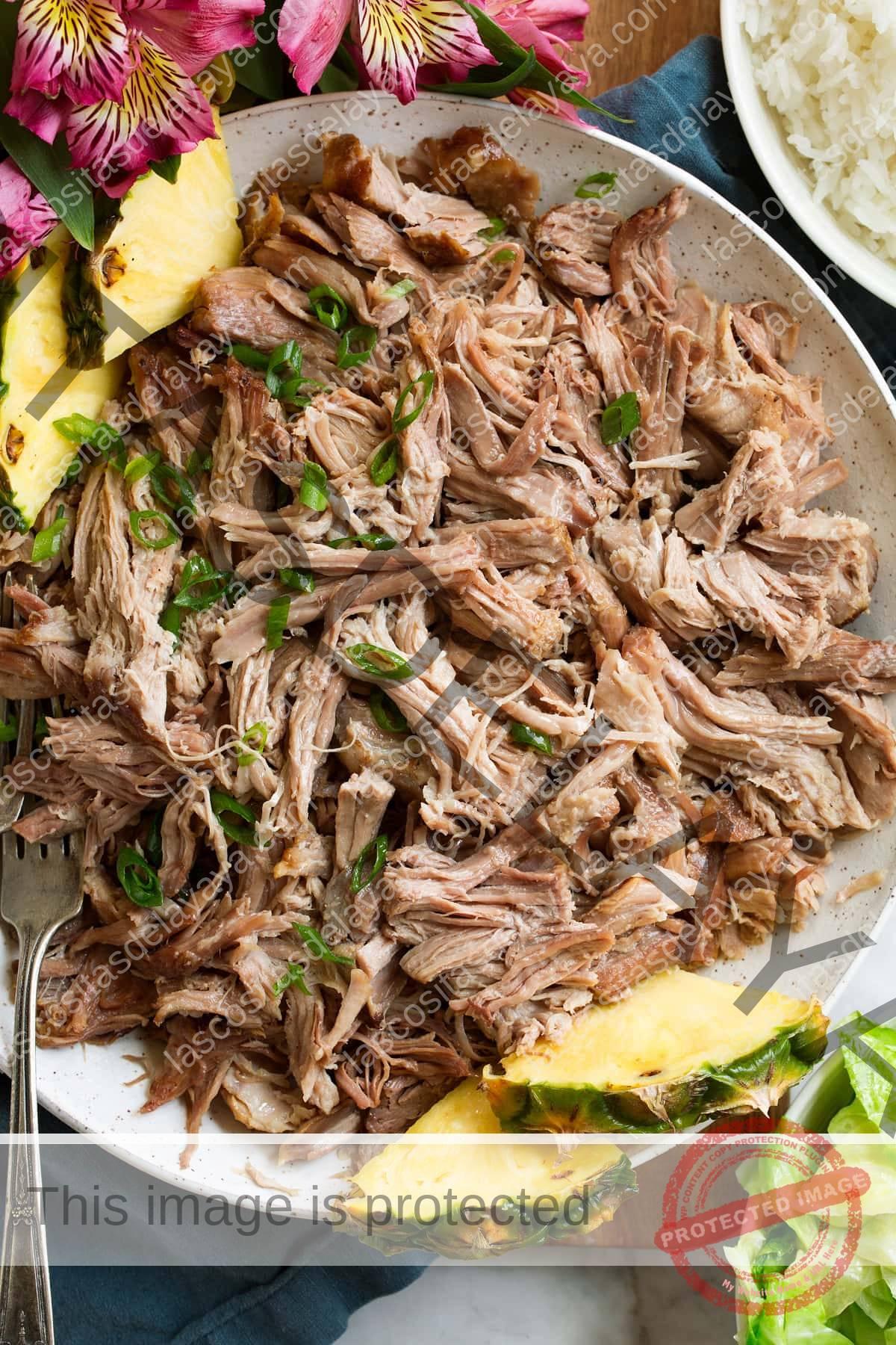 Imagen aérea de carne de cerdo Kalua desmenuzada en un tazón de servir blanco con piña.  Se adorna con cebollino en rodajas.