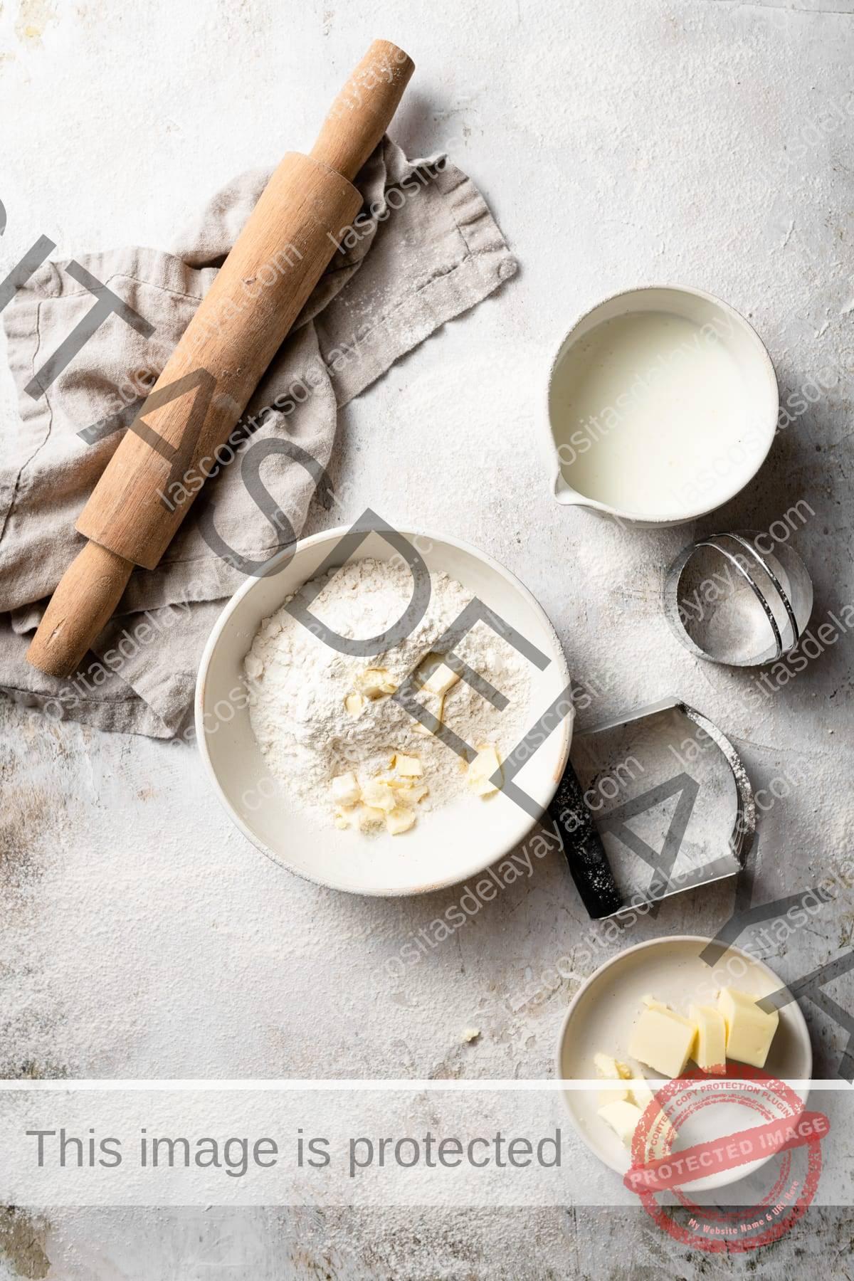 Mostrando los ingredientes de la galleta, incluida la mezcla de harina, mantequilla y suero de leche en tazones para mezclar. Rodillo en el lateral y paño de cocina beige.
