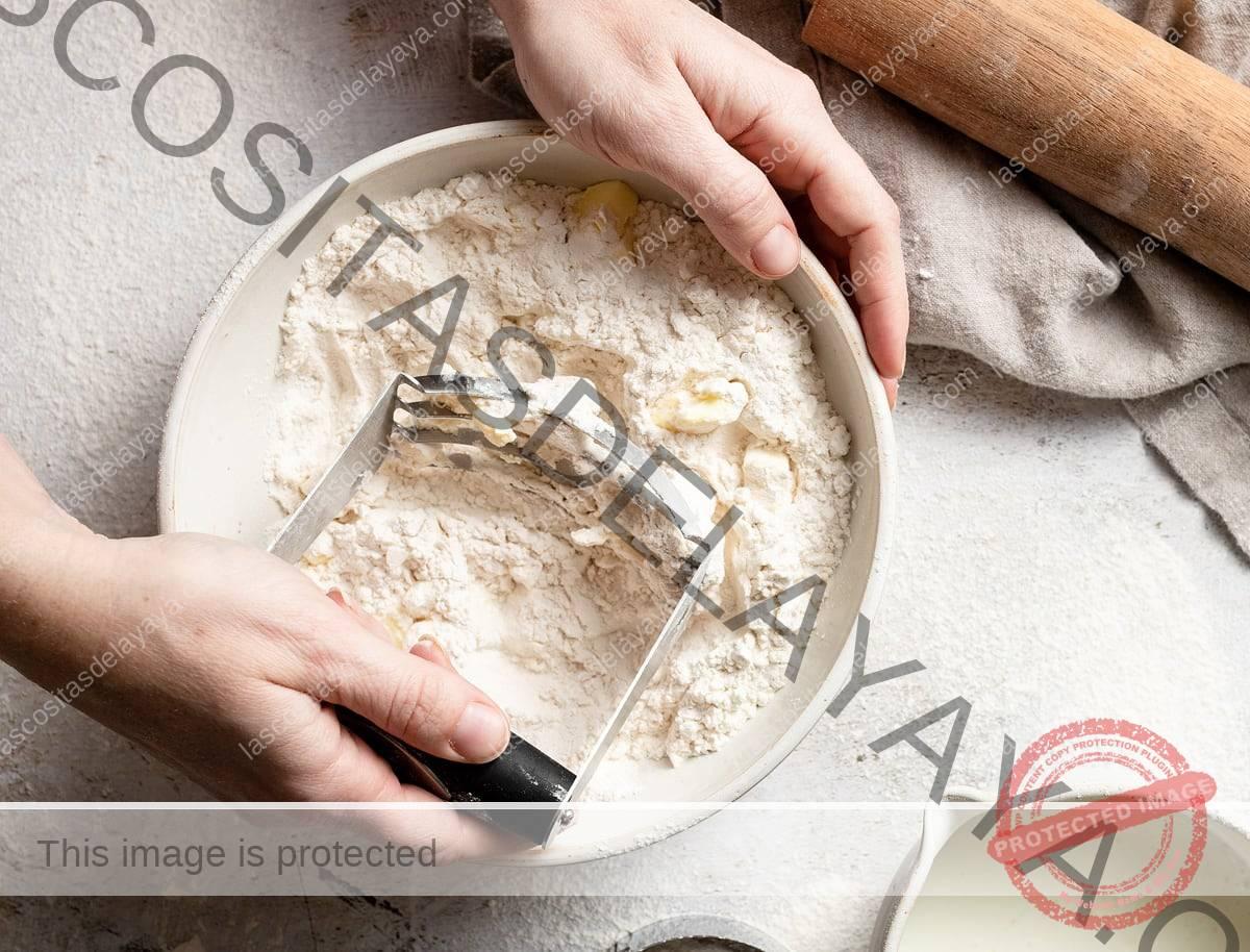 Muestre cómo hacer galletas cortando la mantequilla en la mezcla de harina con un cortador de masa.