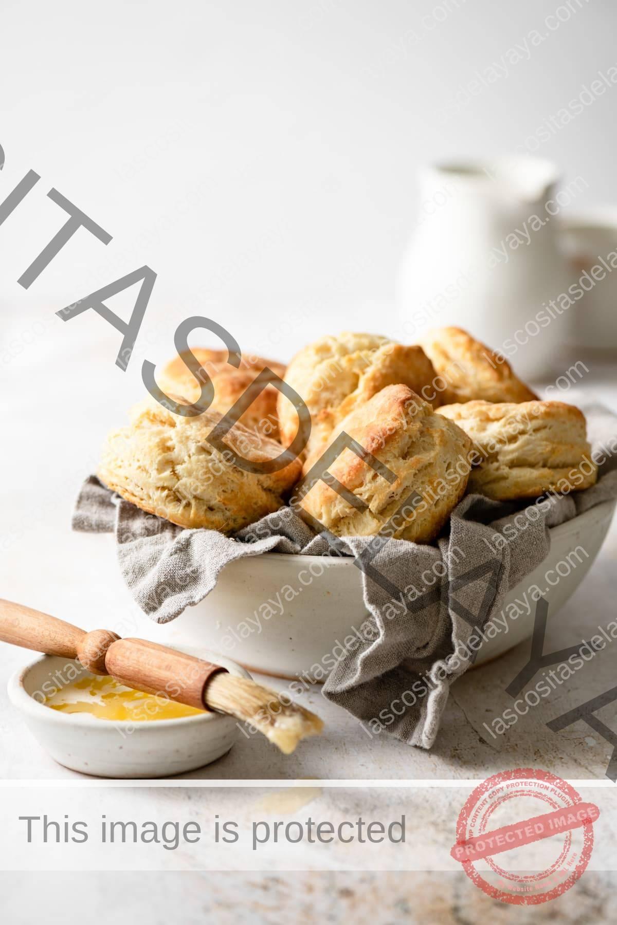 Cuenco lleno de galletas de suero de leche con un cepillo y mantequilla a un lado.