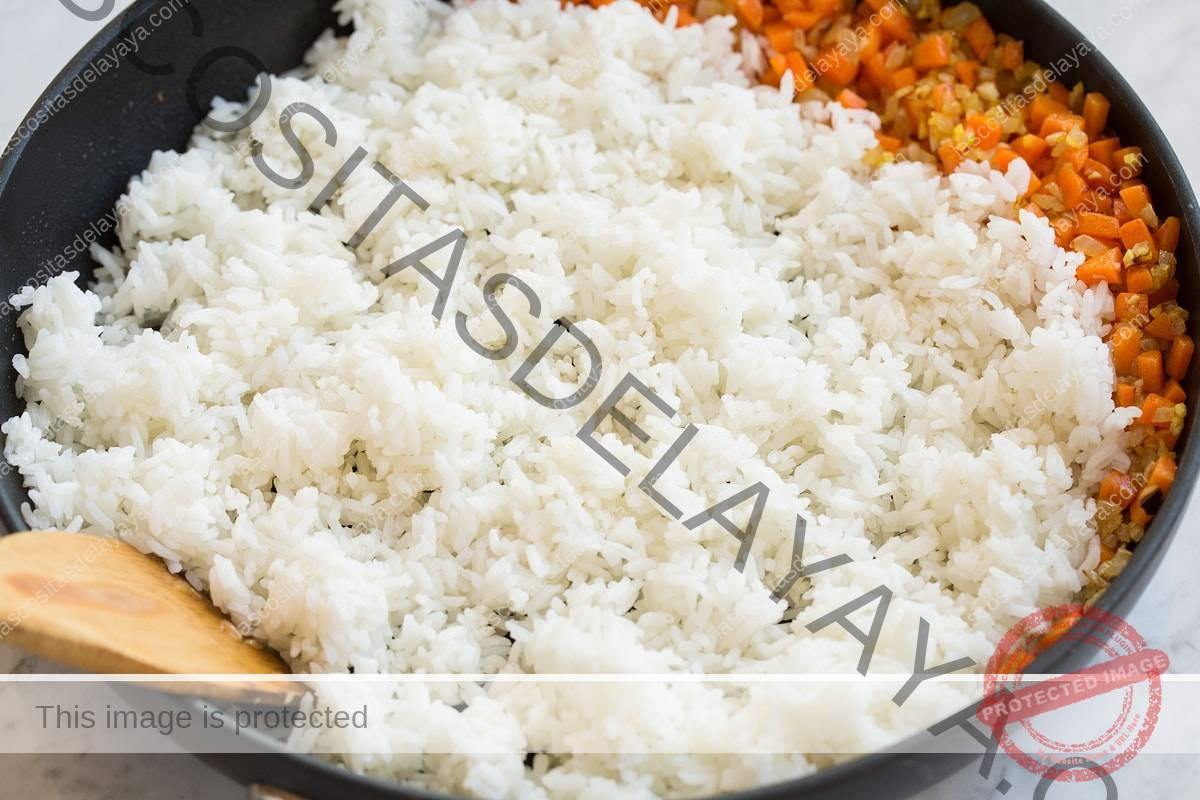 Freír arroz blanco en una sartén con verduras.