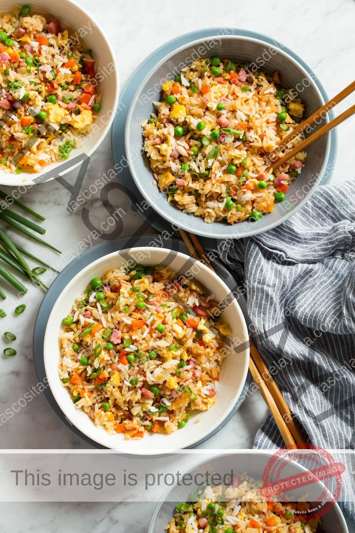 Cuatro porciones de arroz frito que se muestran en la parte superior en tazones blancos colocados en platos azules con palillos a un lado.