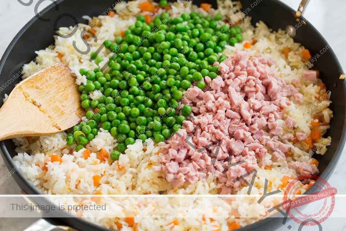 Se agregan guisantes y jamón a la mezcla de arroz frito.