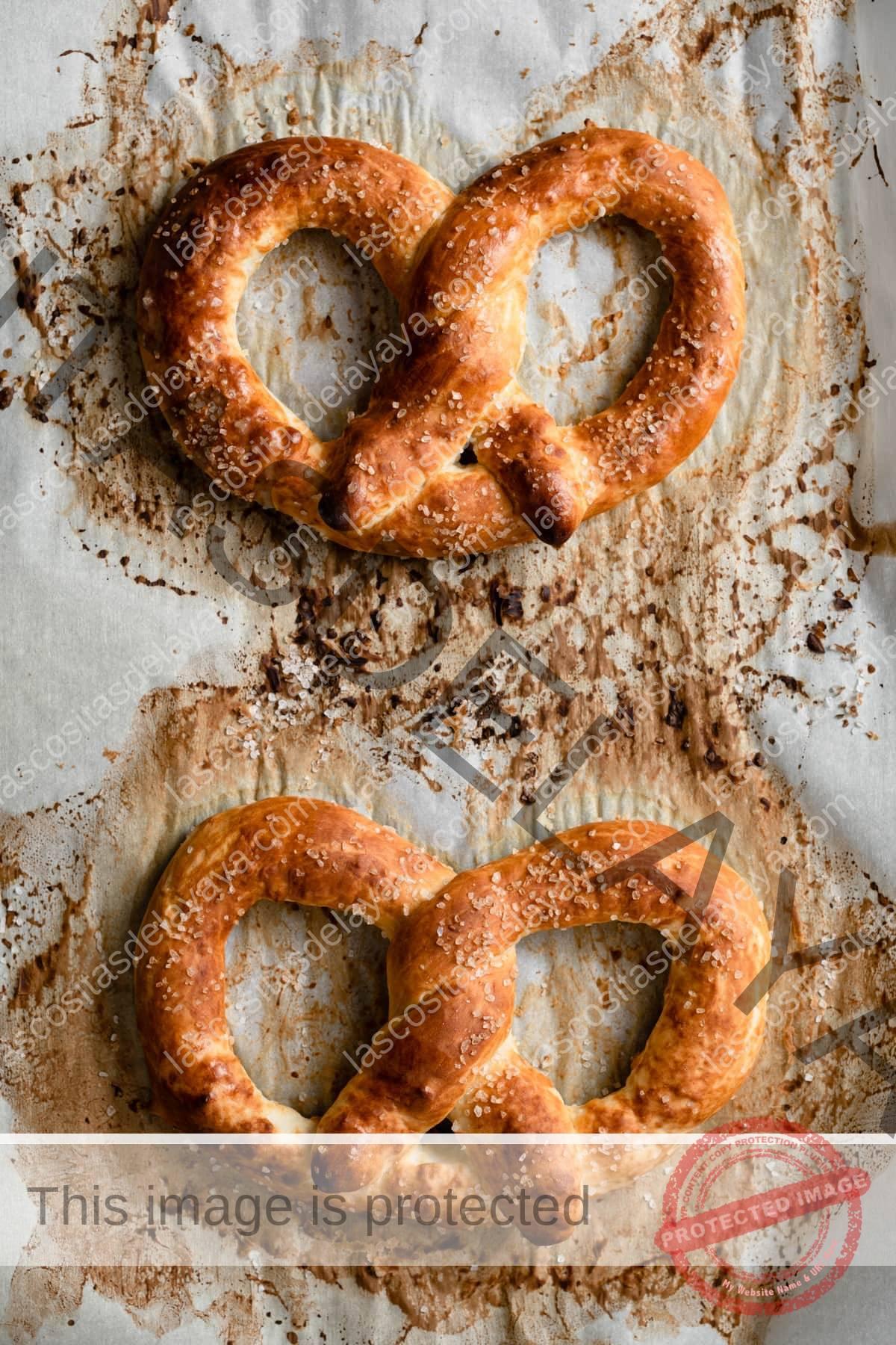 Dos pretzels en una bandeja para hornear forrada con papel pergamino que muestra cómo deben verse después de horneados en un color marrón dorado.