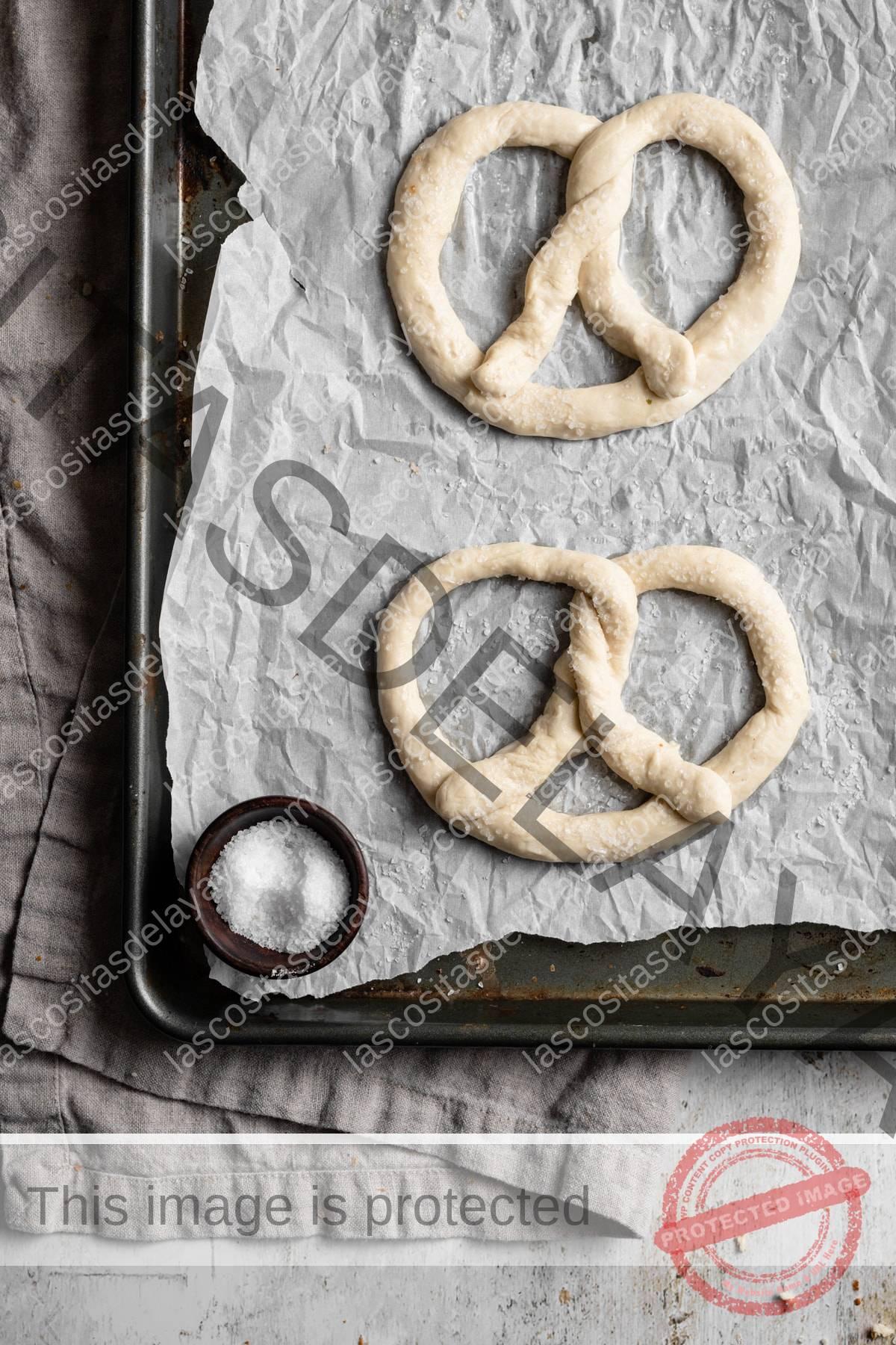 Imagen que muestra cómo hacer pretzels suaves.  Dale forma a la masa en forma de pretzel y se colocan en una bandeja para hornear forrada con papel pergamino para hornear.