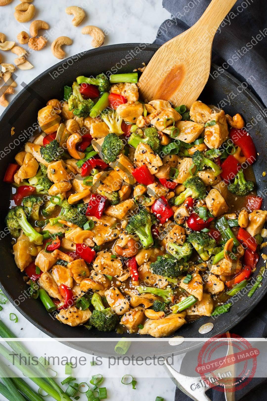 Pollo con anacardos que se muestra aquí en la sartén.  Incluye trozos de pechuga de pollo, brócoli, pimientos y una salsa dulce y picante.