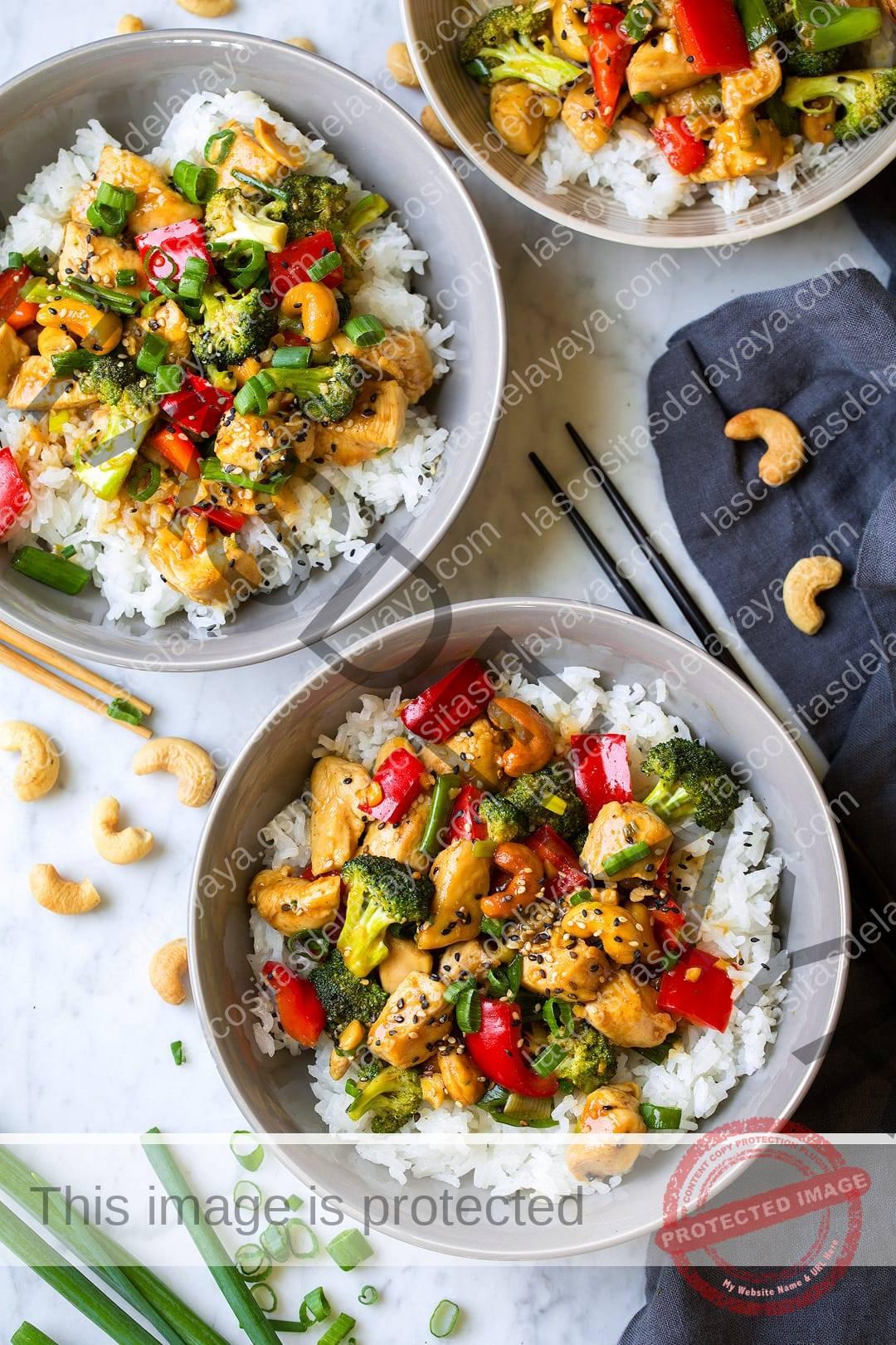 Pollo con anacardos servido en tres cuencos sobre arroz blanco.
