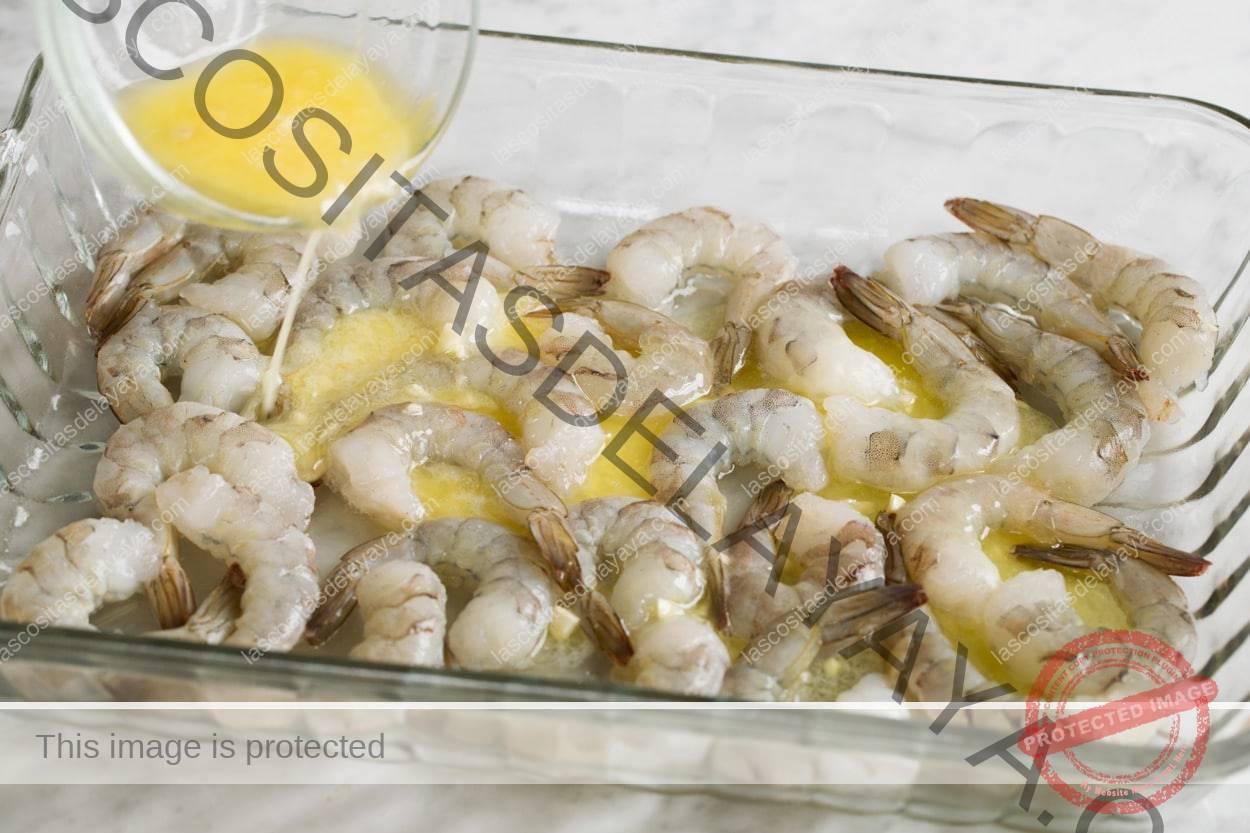 Mostrando cómo hacer camarones asados.  Vierta el ajo y la mantequilla de limón sobre los camarones en la bandeja para hornear.