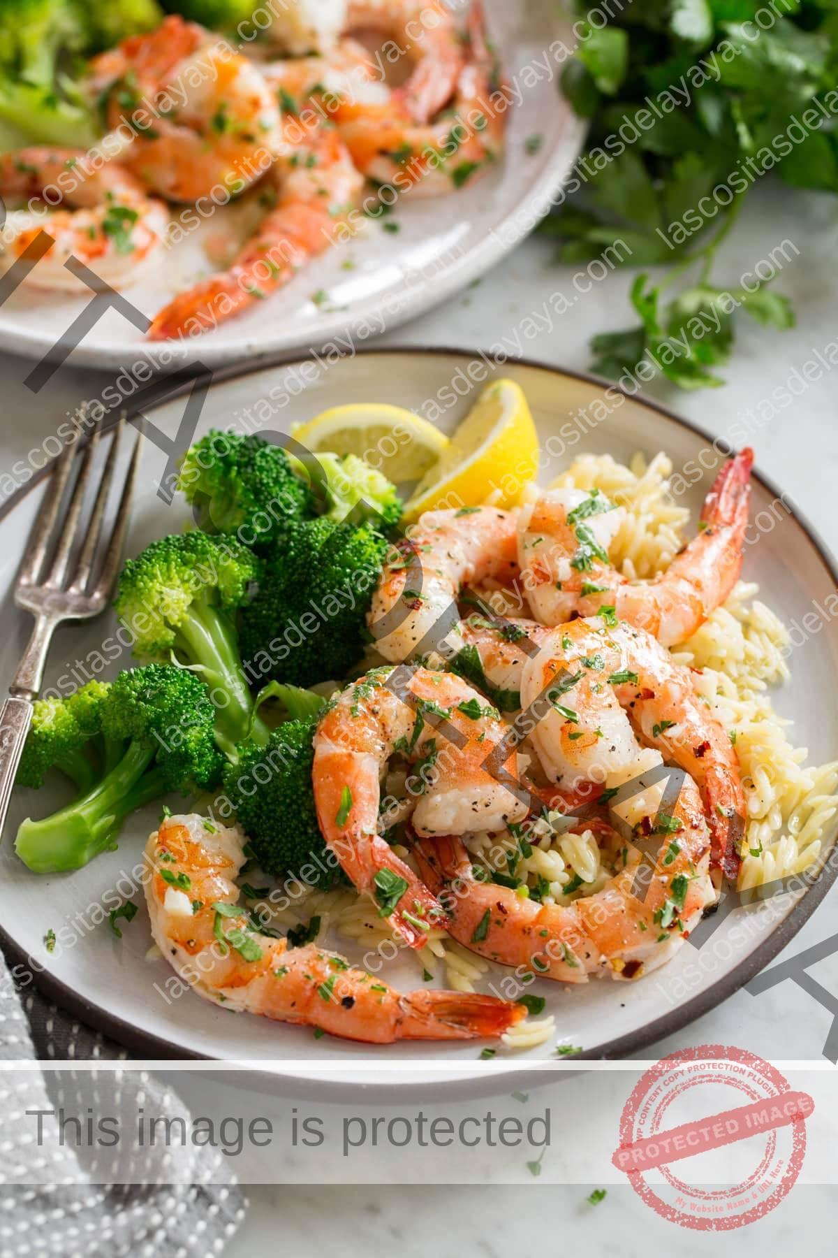 Camarones al horno en plato blanco con orzo y brócoli.