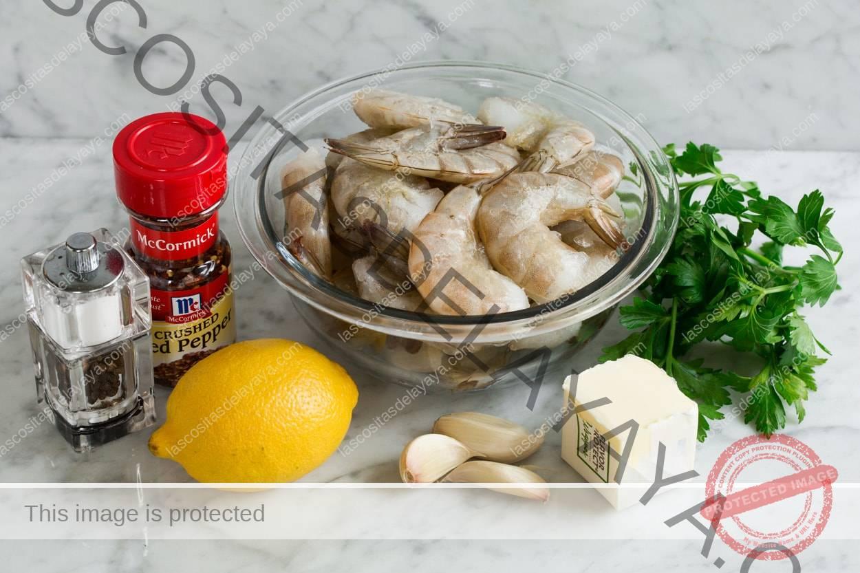 Los ingredientes necesarios para hacer camarones asados que se muestran aquí, incluyen camarones crudos, mantequilla, ajo, limón, perejil, hojuelas, sal y pimienta.