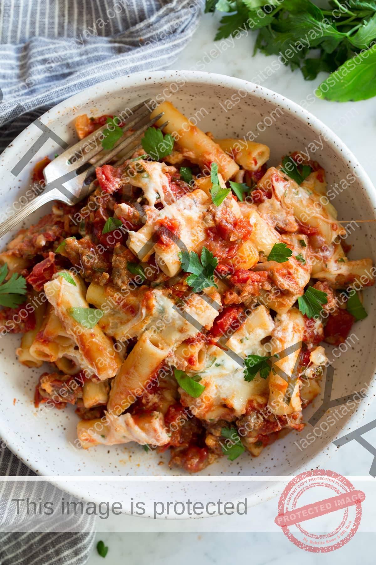Tazón de ziti al horno que incluye pasta ziti, salchicha, salsa marinara, tres tipos de queso italiano y hierbas frescas.