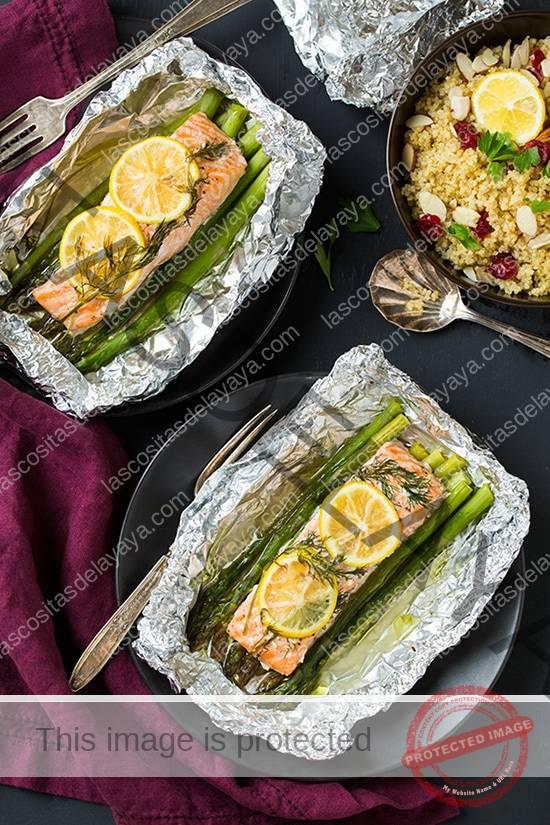 Dos platos de salmón y espárragos cubiertos con rodajas de limón