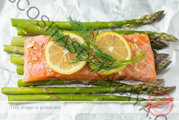 Agrega rodajas de limón y eneldo fresco sobre el filete de salmón.