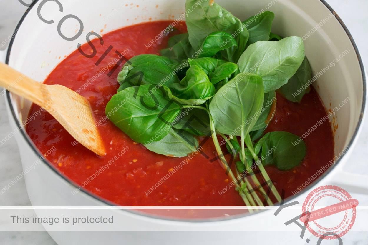 Adicionar tomate esmagado e manjericão fresco à panela.