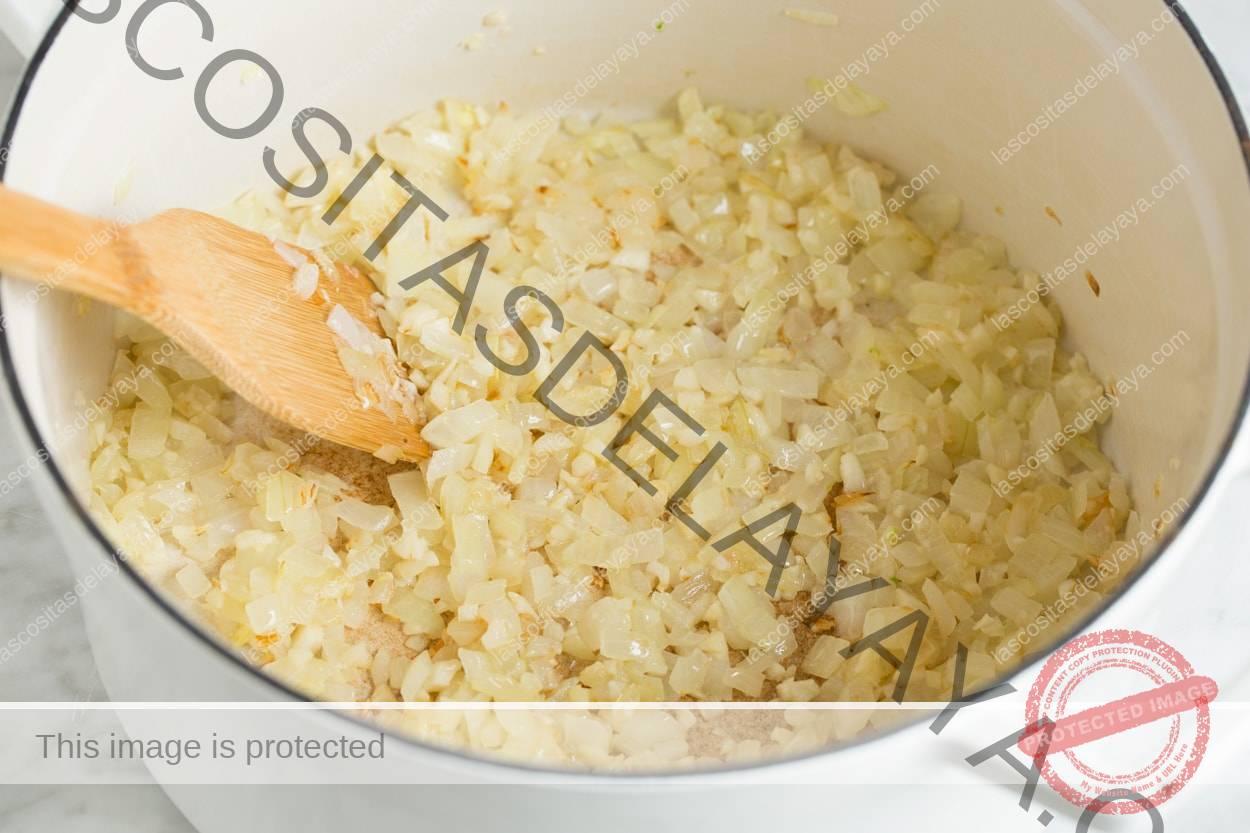 Refogue a cebola e o alho em uma panela branca grande.