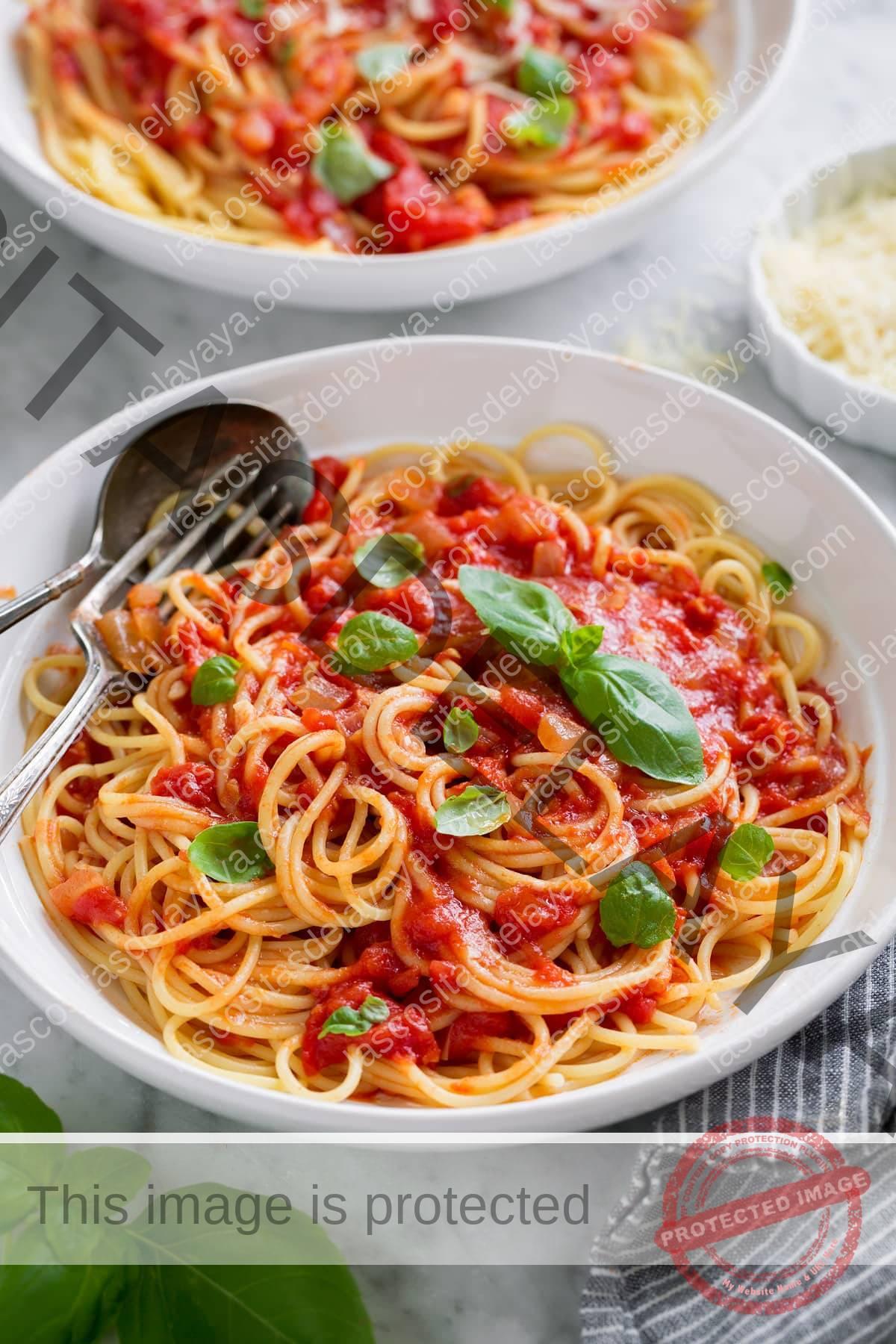 Molho Marinara servido com espaguete, parmesão e manjericão fresco. Mostrado em uma tigela de massa branca.