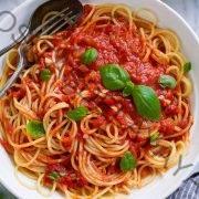 Molho Marinara misturado com espaguete em uma tigela de macarrão.