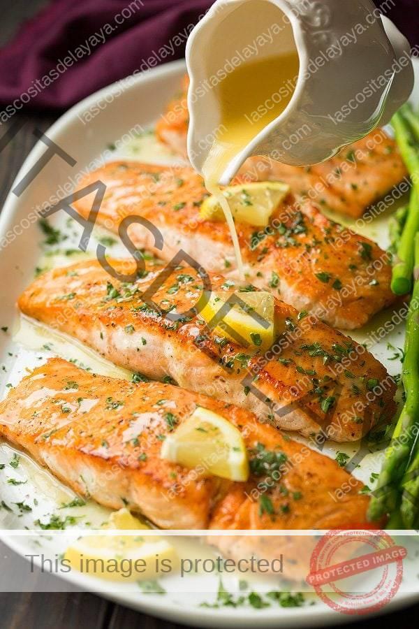 Vierta la salsa de mantequilla de limón sobre los filetes de salmón frito en una fuente blanca.
