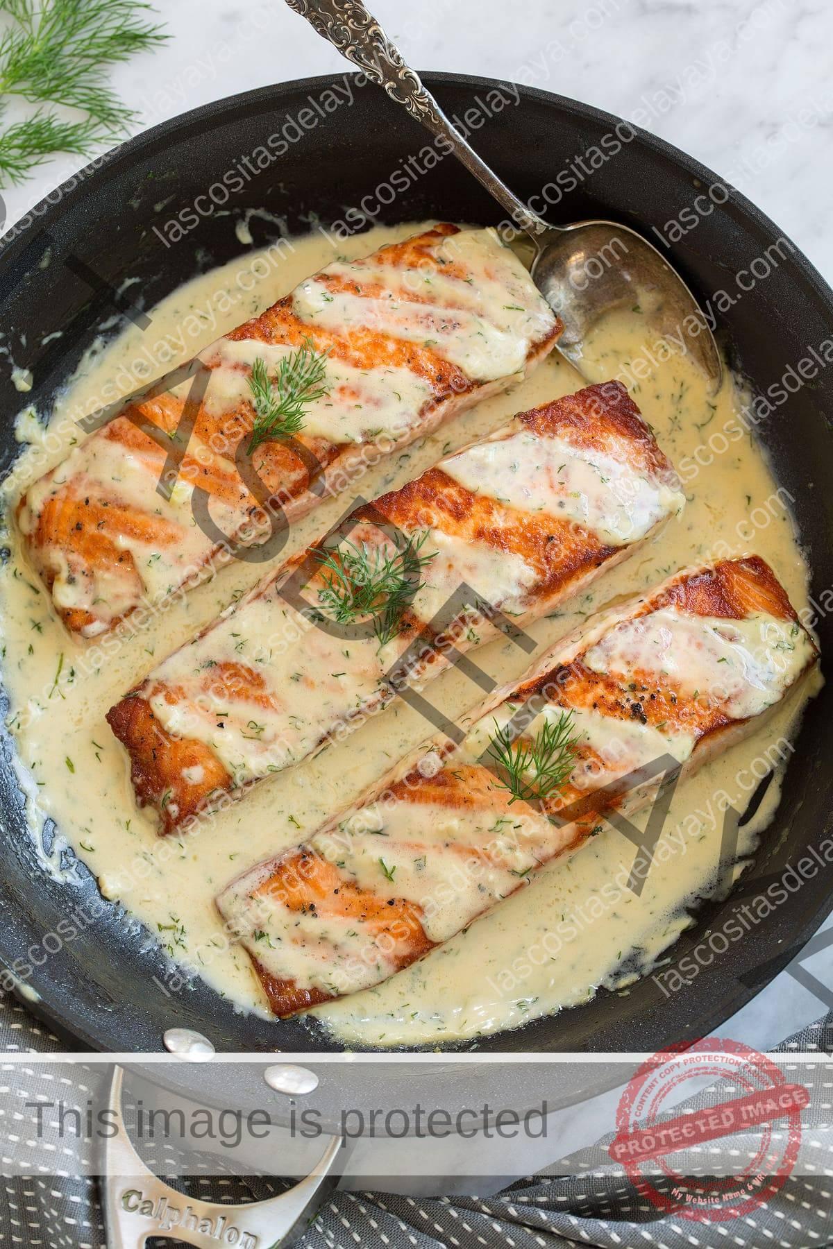 Tres filetes de salmón en una sartén con salsa cremosa de dijon.