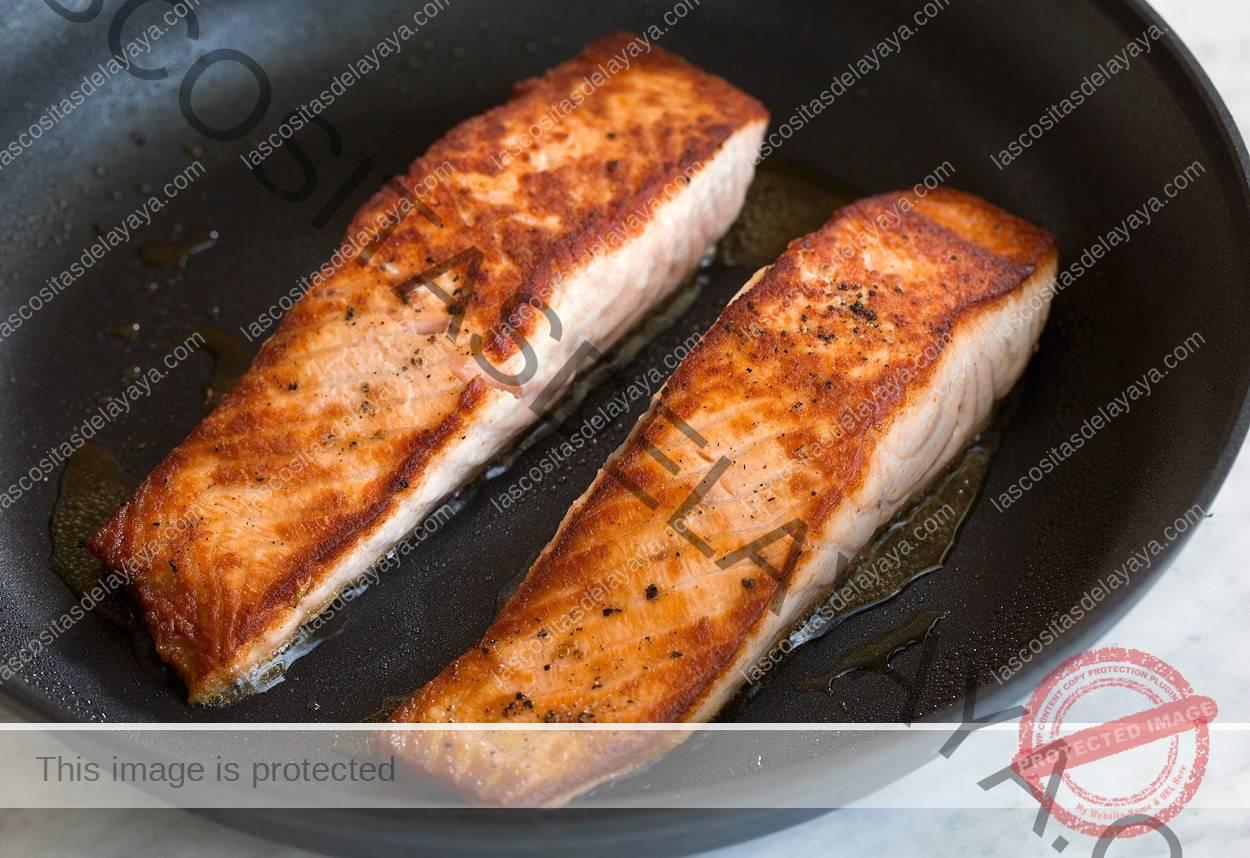 Dos filetes de salmón a la parrilla en una sartén de color marrón dorado que se muestra aquí en una sartén antiadherente grande.