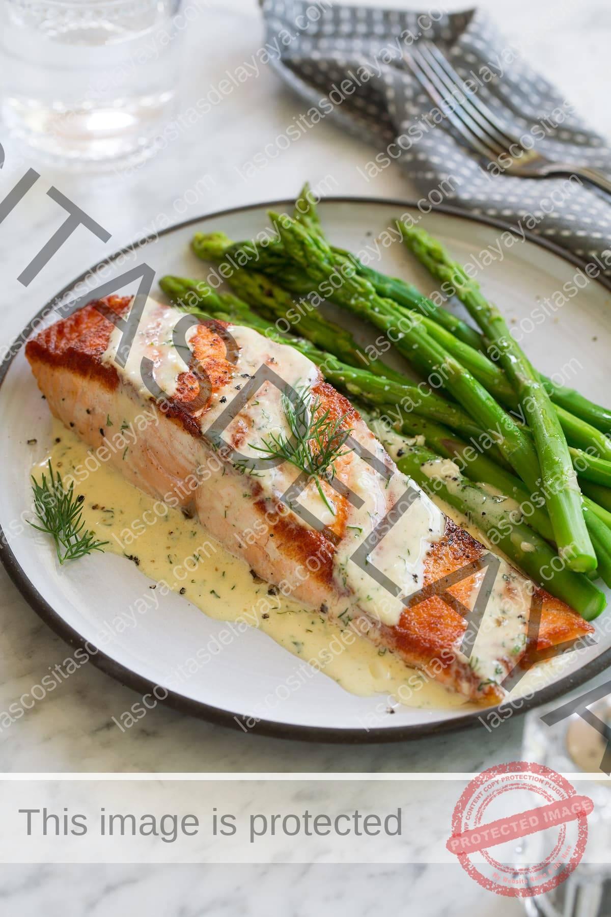 Filete de salmón en un plato blanco colocado sobre una superficie de mármol.  Cubierto con salsa dijon y servido con espárragos.