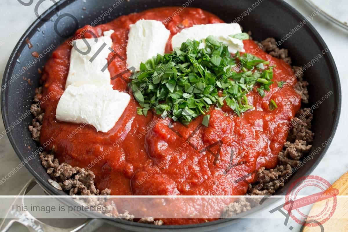 Agregue salsa marinara, queso crema y albahaca fresca a la carne molida en la sartén.