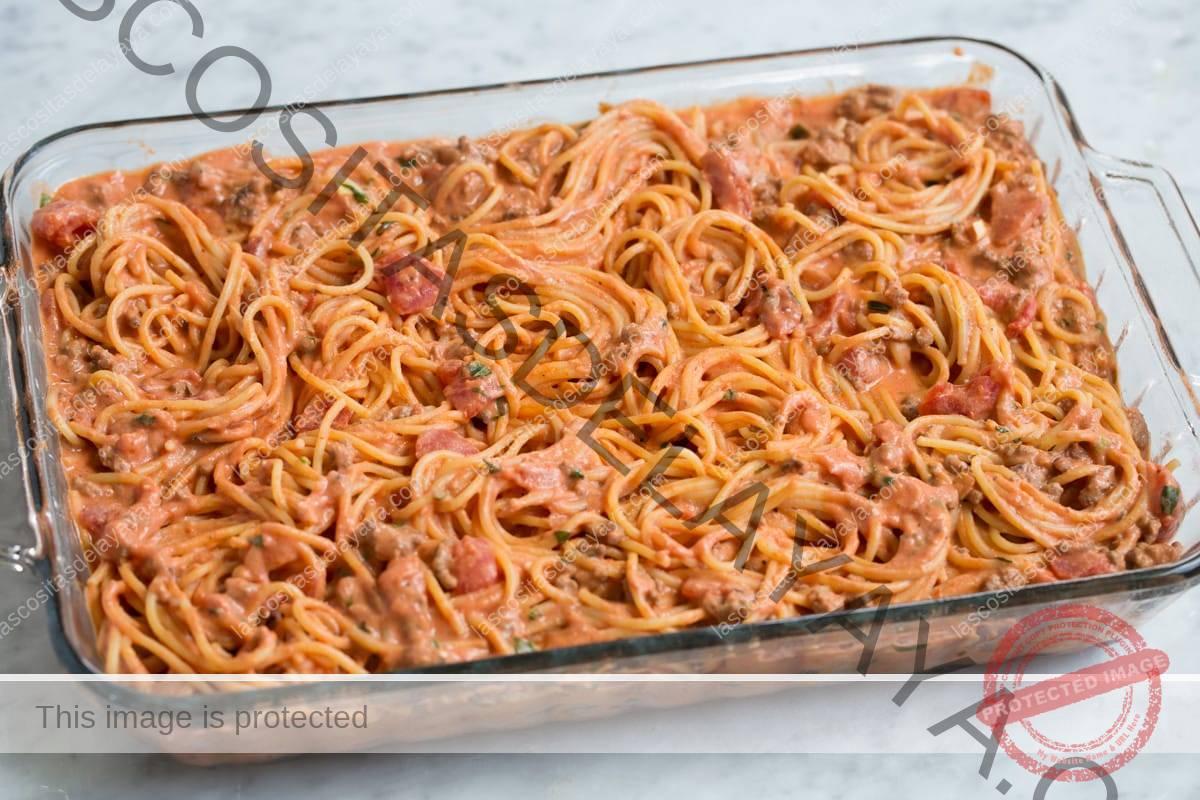 Se muestran los espaguetis asados antes de hornear en el horno.