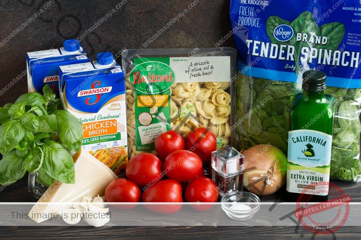 Ingredientes necesarios para hacer la sopa de tortellini que se muestra aquí, incluidos tortellini, espinacas, tomate, cebolla, parmesano, ajo, caldo de pollo, albahaca, aceite de oliva.