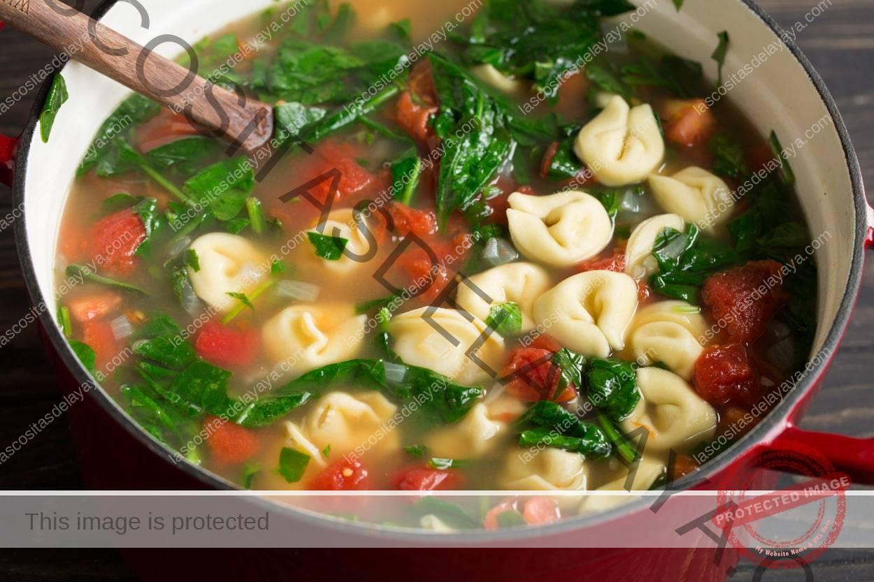 Complete la sopa de tortellini en una sartén grande de hierro fundido rojo con una cuchara de madera.
