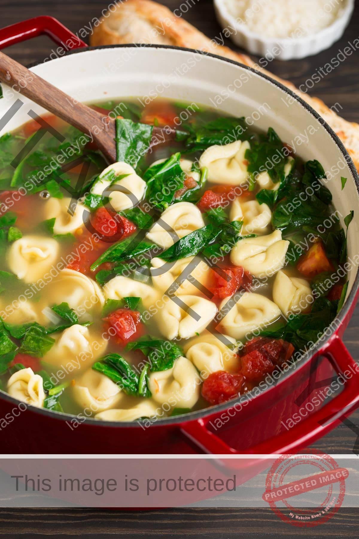 Cerrar imagen de sopa de tortellini en una sartén roja sobre una mesa de madera.