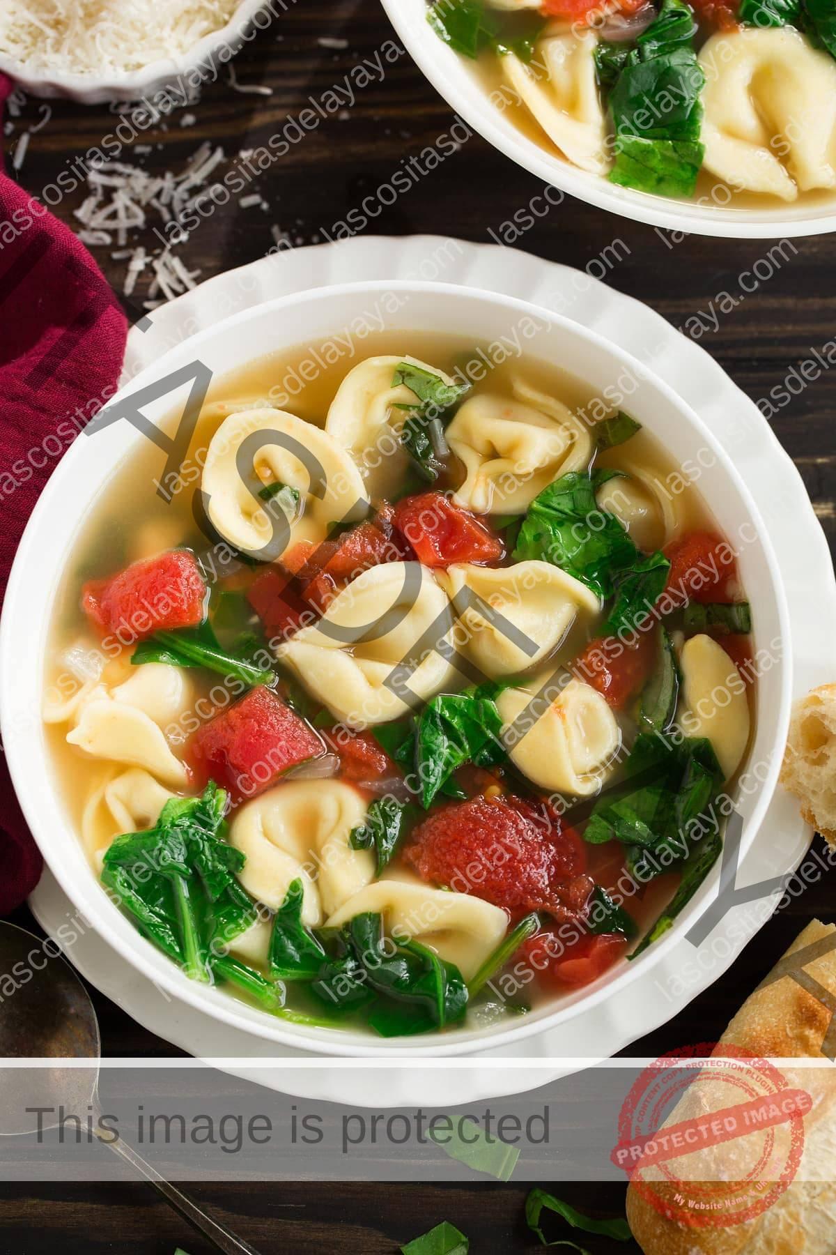 Imagen aérea de sopa de tortellini en un tazón de servir blanco.