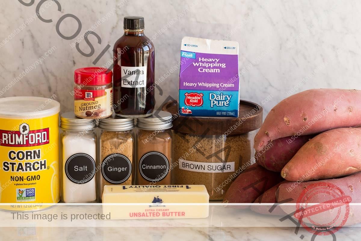 Imagen de los ingredientes utilizados para hacer ñame caramelizado.  Incluye batatas, azúcar morena, crema, mantequilla, canela, nuez moscada, jengibre, sal, vainilla y maicena.
