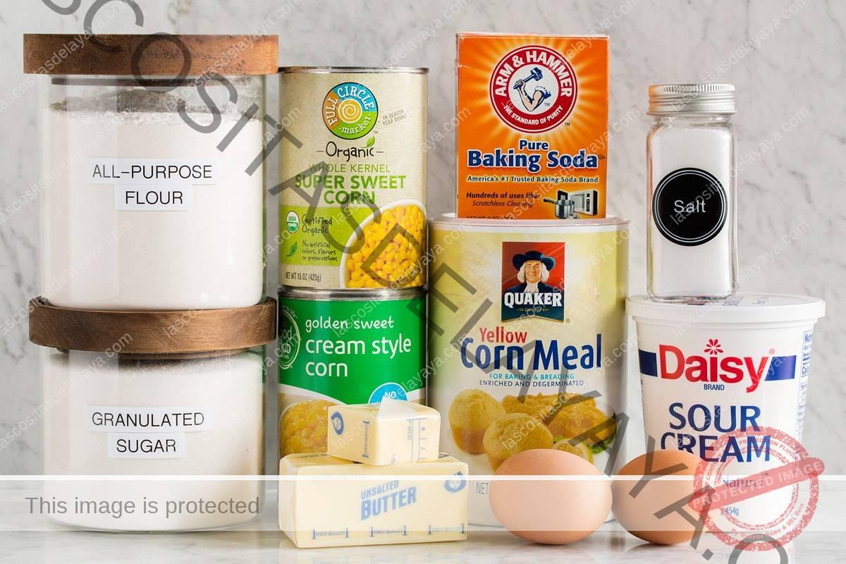 Imagen de los ingredientes necesarios para hacer la cazuela de maíz desde cero.  Incluye maíz enlatado y crema de maíz, harina, azúcar, bicarbonato de sodio, crema agria, harina de maíz, sal, huevos y mantequilla.