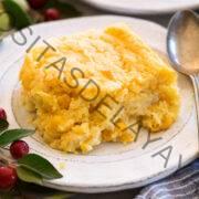 Una porción de cazuela de maíz que se muestra en un plato blanco con una cuchara al lado.