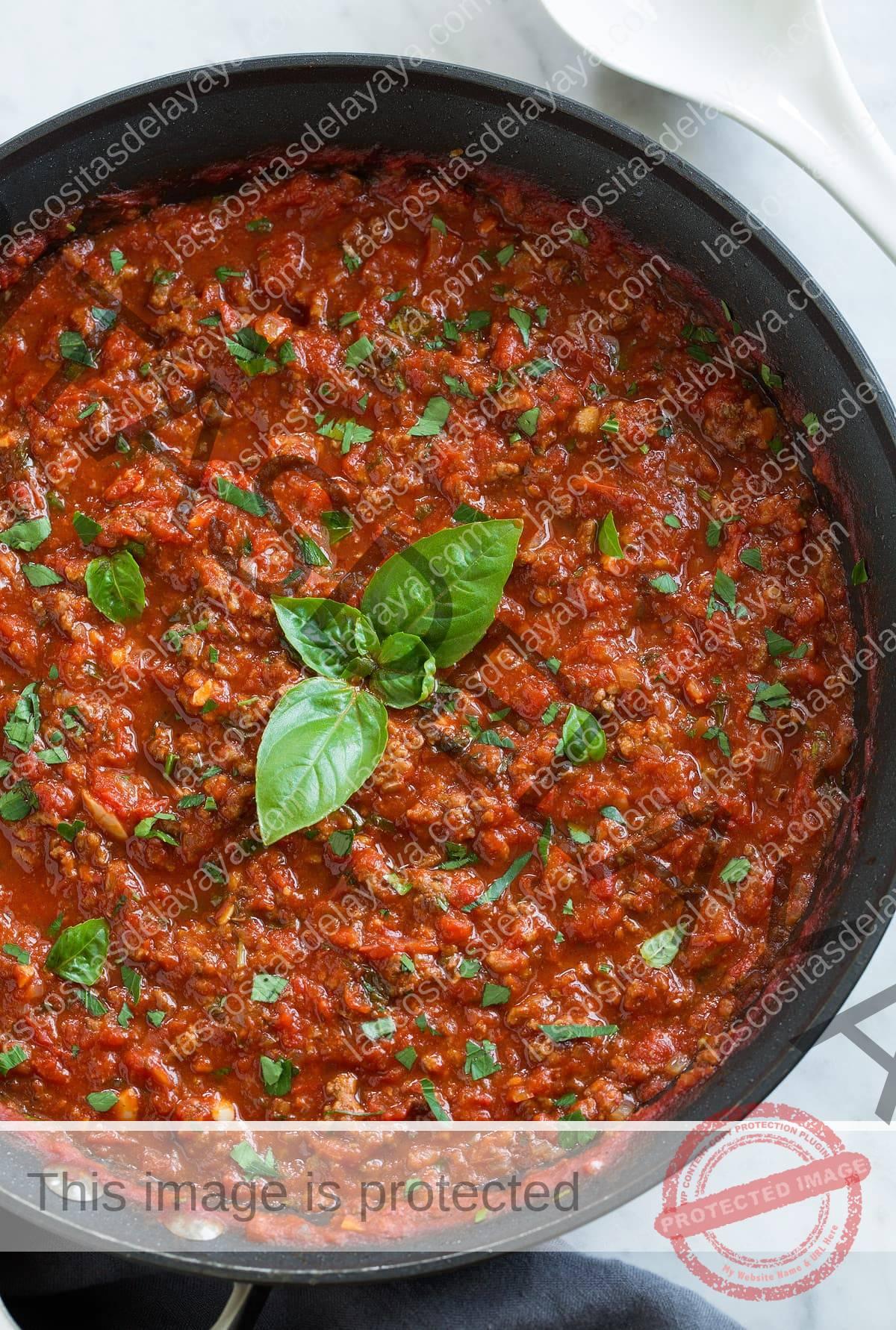 Arriba, imagen aproximada de la mejor salsa para espaguetis desde cero en una sartén con hojas de albahaca en el centro.