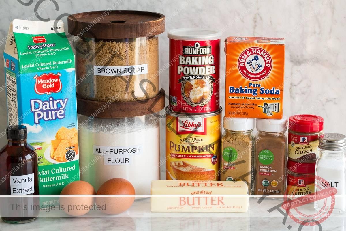 Imagen de los ingredientes utilizados para hacer tortitas de calabaza.  Muestra harina, azúcar morena, sal, levadura en polvo, bicarbonato de sodio, especias, mantequilla, suero de leche, huevos y vainilla.