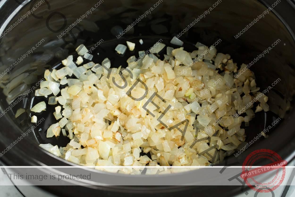Mostrando los pasos para hacer chile.  Agregue las cebollas salteadas a la sartén eléctrica para hacer chile.