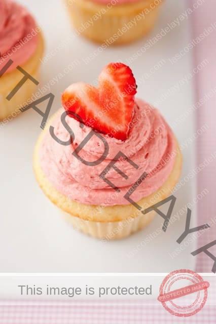 Cupcake de pastel de fresa cubierto con crema de mantequilla de fresa y una fresa en rodajas