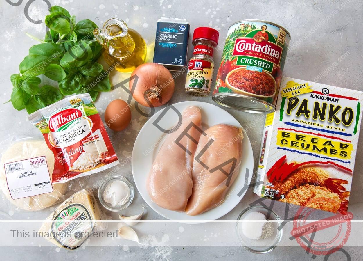 Ingredientes necessários para o parmesão de frango mostrados aqui, incluindo panko, peitos de frango, tomates triturados, orégano, alho seco e fresco, cebola, ovo, azeite, manjericão, mussarela, provolone, parmesão e farinha.