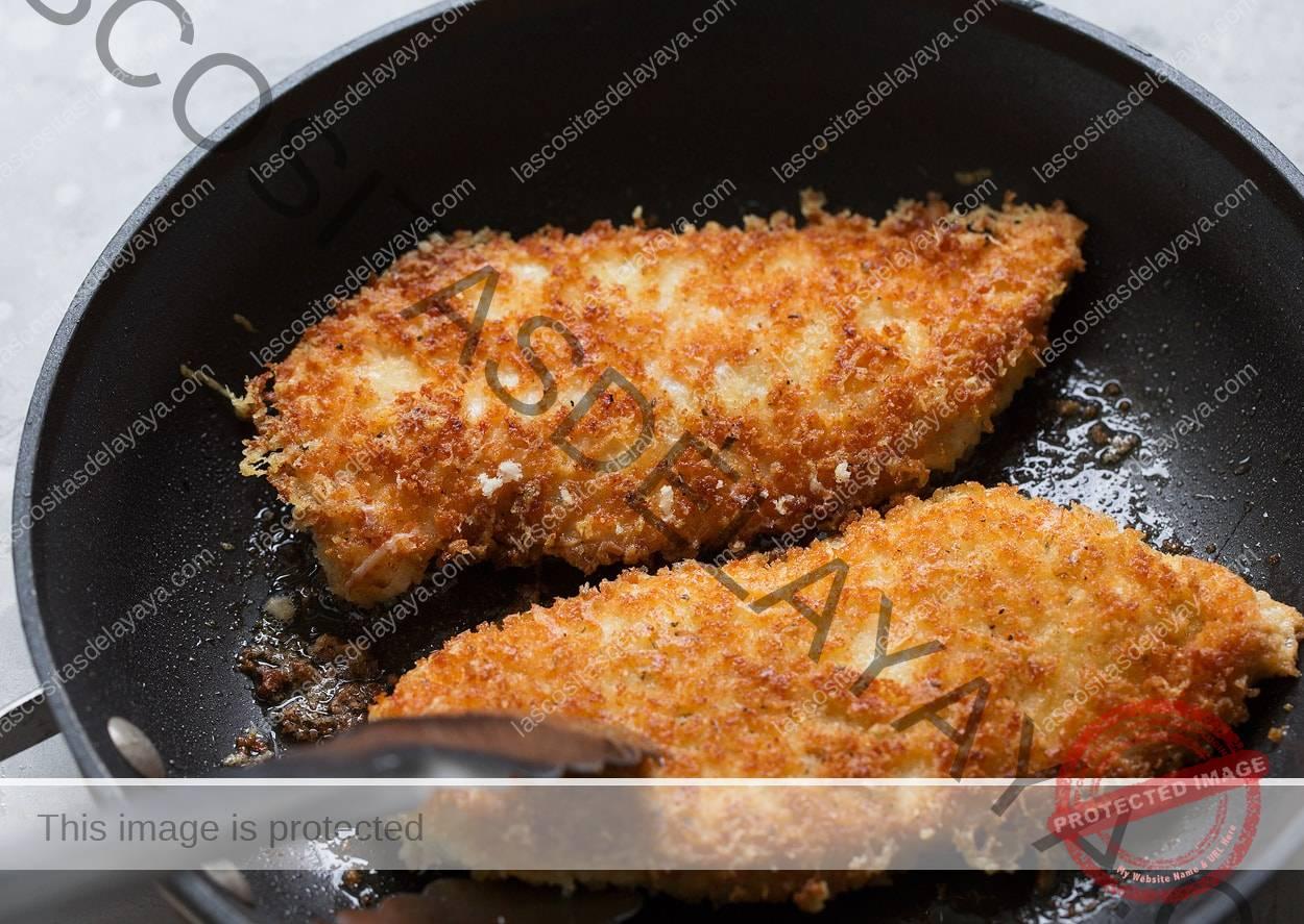 Tostar pedaços de parmesão de frango no azeite na frigideira antiaderente preta até dourar.