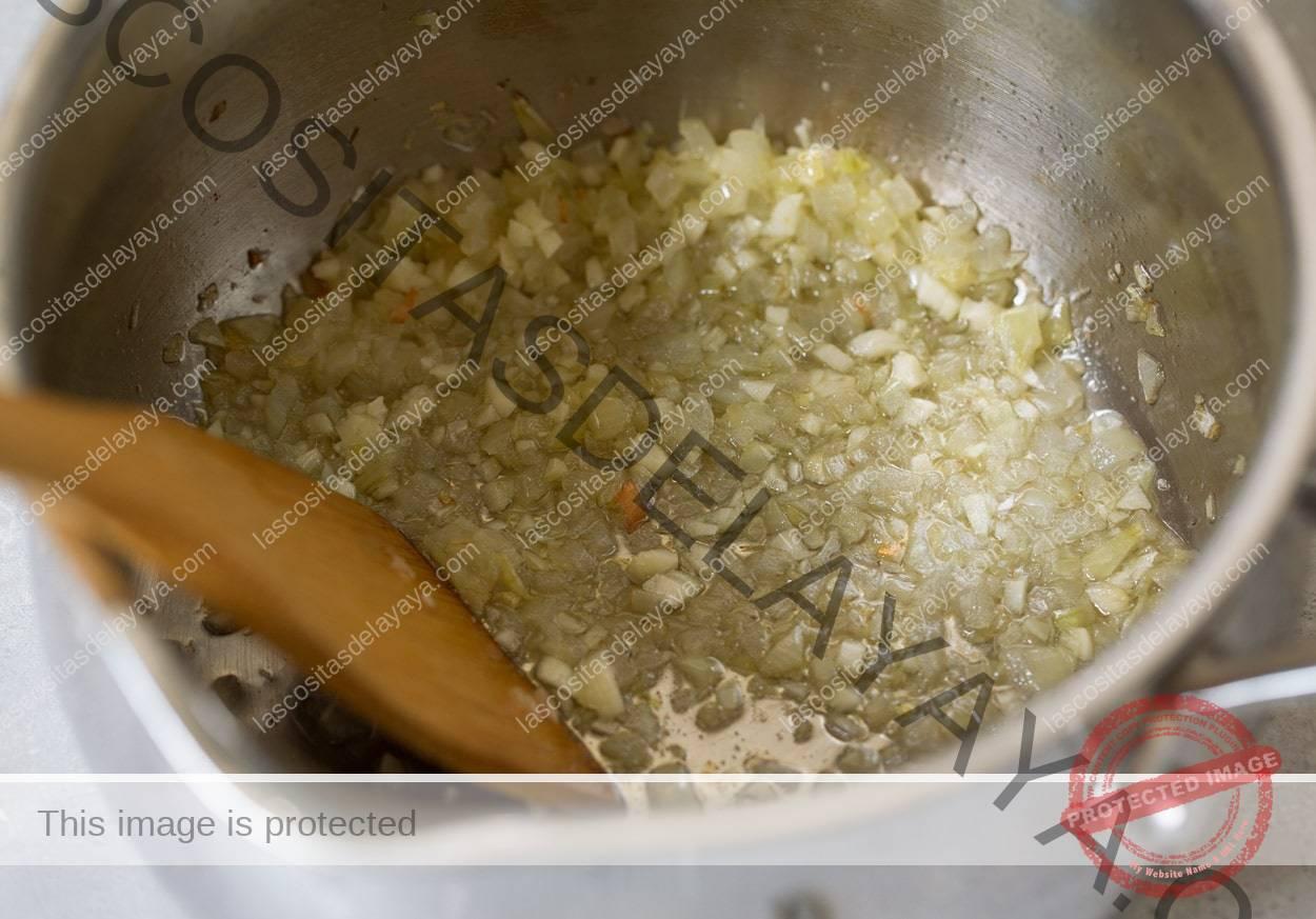 Cebola salteada e alho em uma panela para frango parmesão marinara.