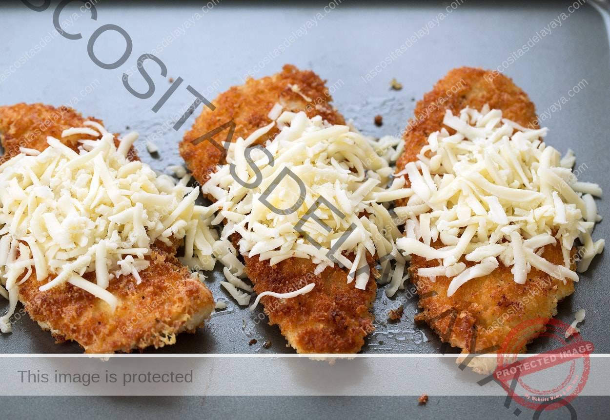 Colocar costeletas de frango douradas na assadeira e cobrir com os queijos ralados.