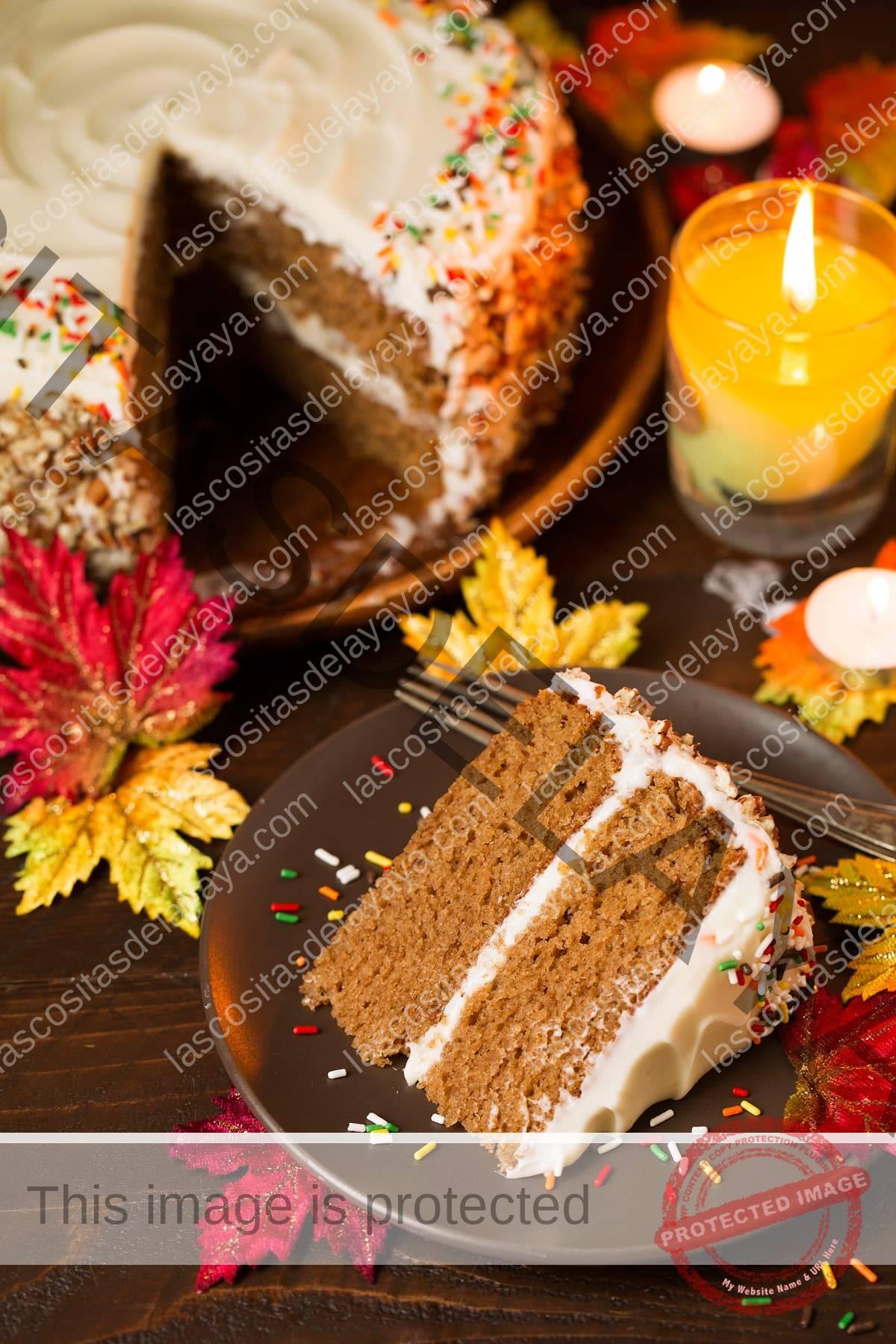Una rebanada de bizcocho de especias en un solo plato y un bizcocho de especias entero de fondo.  Las decoraciones de la imagen incluyen hojas de otoño, una vela encendida y una superficie de madera.