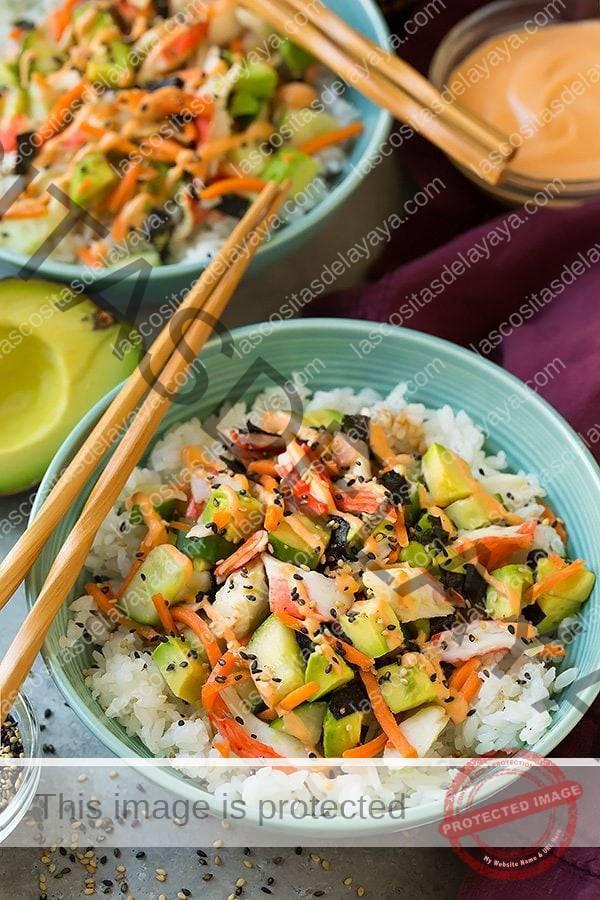 Ingredientes de California roll en capas en un tazón turquesa con palillos.  Los ingredientes incluyen arroz de sushi, cangrejo, nori, zanahoria, pepino, aguacate, mayonesa picante y semillas de sésamo.