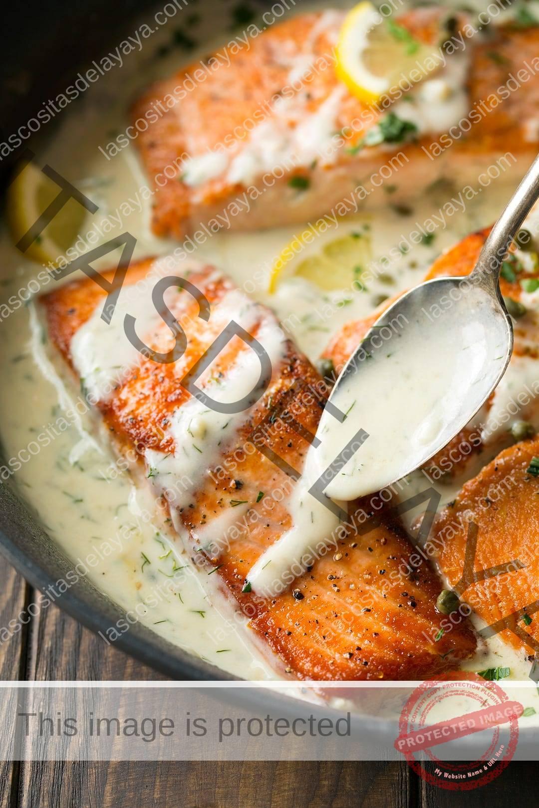 Receta de salmón cocido en una sartén con salsa cremosa de limón y eneldo encima.