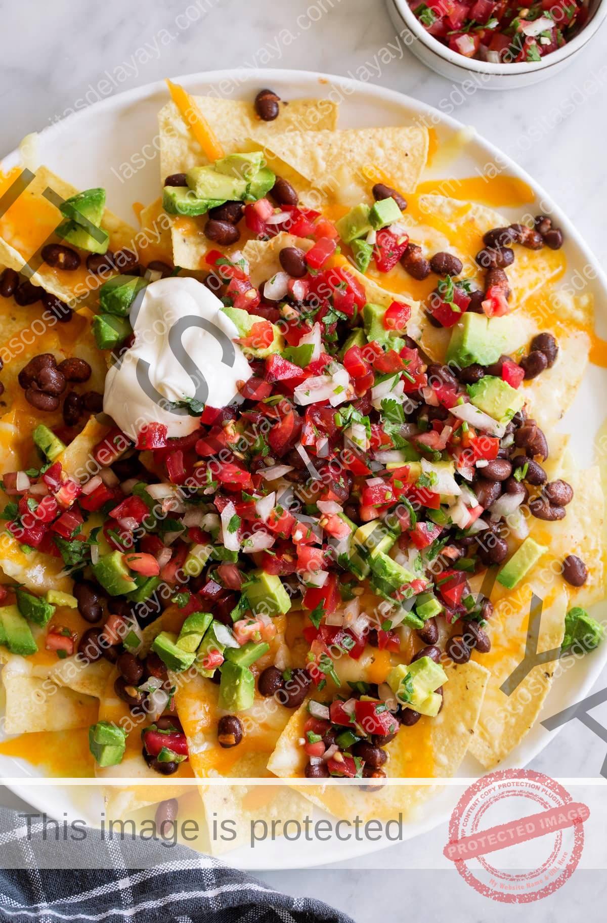 Pico de gallo con nachos junto con queso cheddar derretido, frijoles negros, aguacate cortado en cubitos y crema agria.