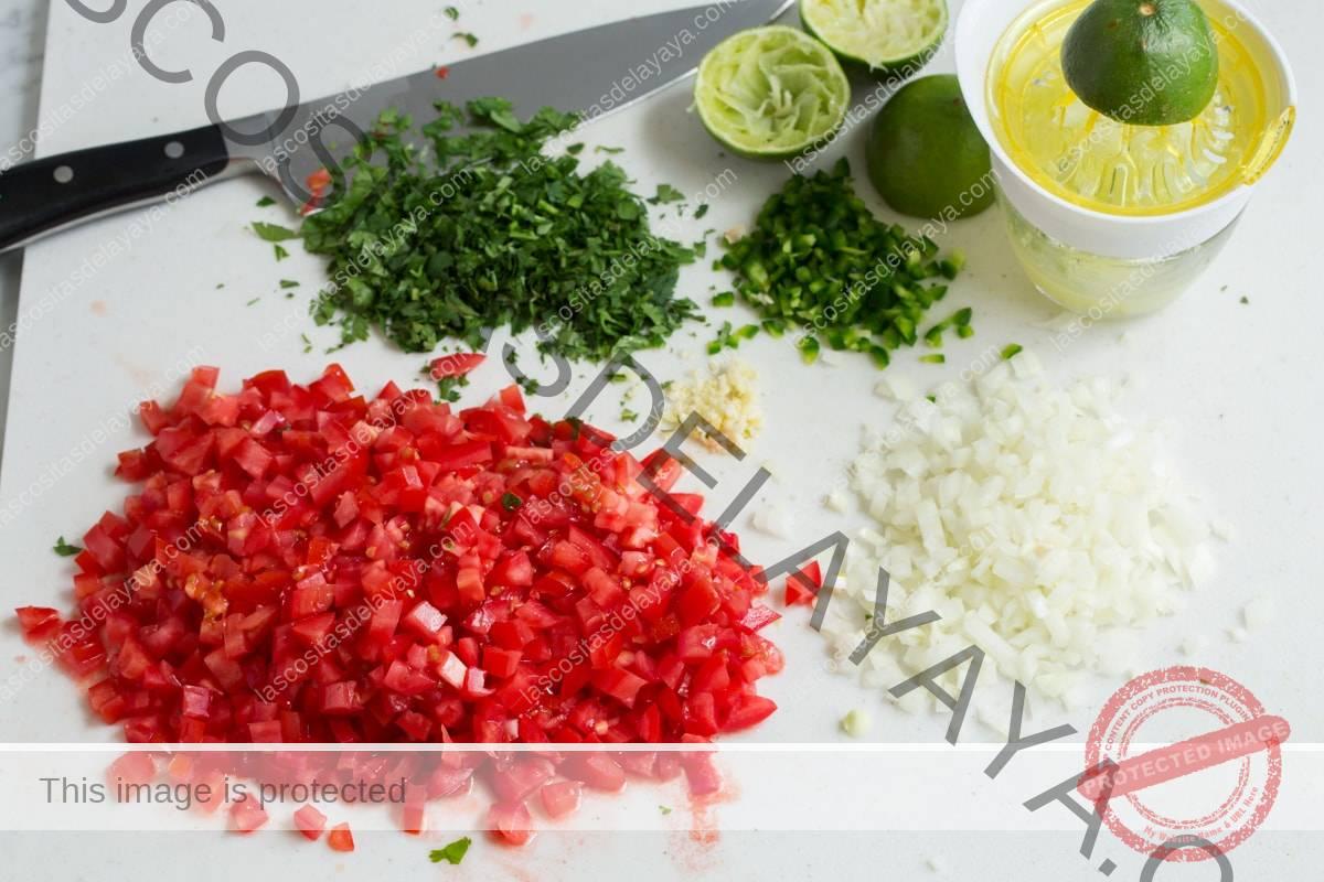 Tomates picados, cebolla, cilantro, chile jalapeño y ajo en una tabla de cortar con un cuchillo en el fondo y un exprimidor.